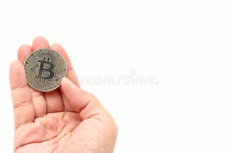 Bitcoin för silver för cryptocurrency för mänsklig hand för ` s hållande på vit isolerad bakgrund med kopieringsutrymme Faktiskt  arkivfoton