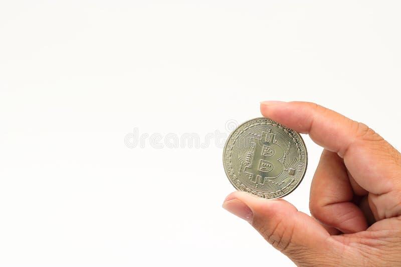 Bitcoin för silver för cryptocurrency för mänsklig hand för ` s hållande på vit isolerad bakgrund med kopieringsutrymme Faktiskt  arkivfoto