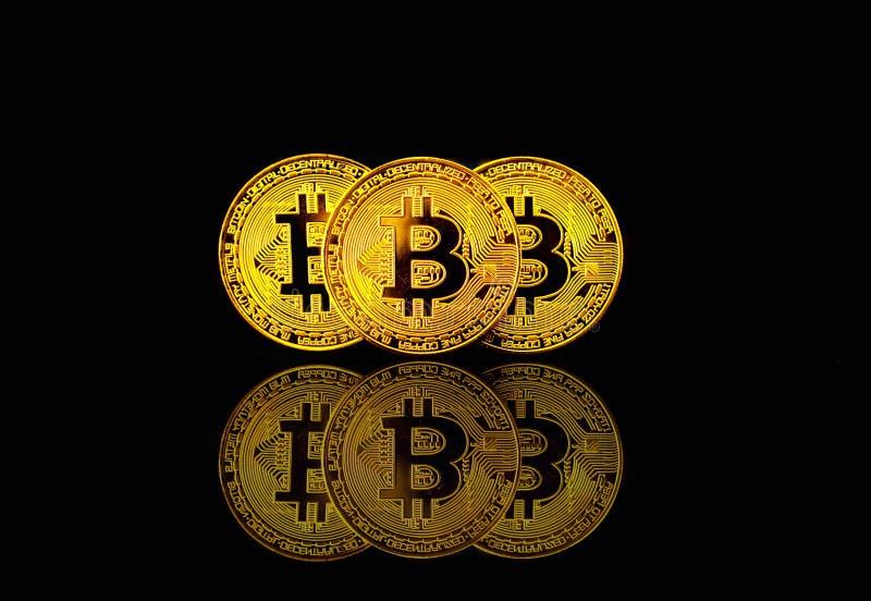 Bitcoin fisico su fondo nero con il chiarore leggero, concetto di cryptocurrency immagini stock