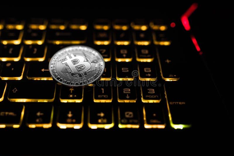 Bitcoin-Gleichgestelltzahlen Münzenlüge auf der schwarzen Tastatur lizenzfreie stockfotos