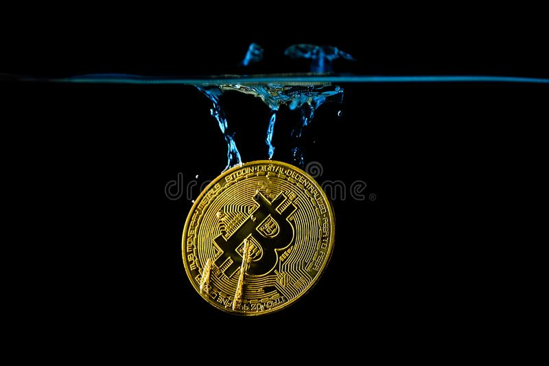 Bitcoin gold coin falling into the water stock image