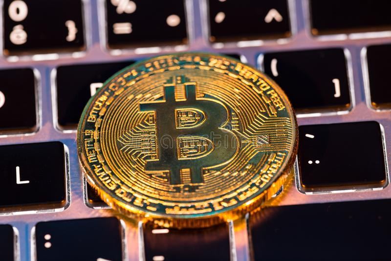 Bitcoin gold coins with laptop keyboard. Virtual cryptocurrency concept. stock photography