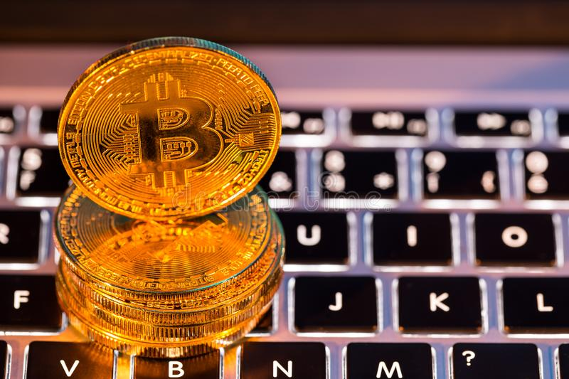 Bitcoin gold coins with laptop keyboard. Virtual cryptocurrency concept. stock image
