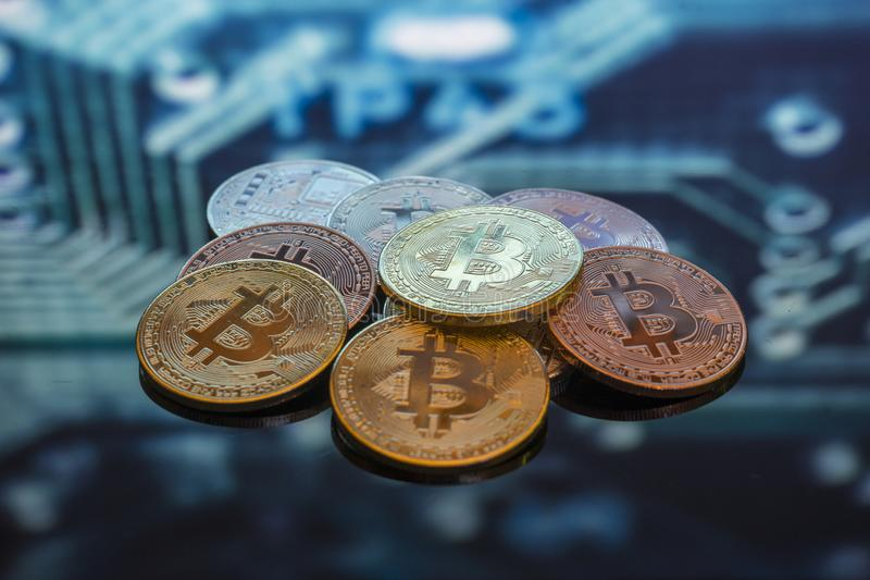 Bitcoin gold, silver and copper coins and defocused printed circuit background. Virtual cryptocurrency concept. stock photography