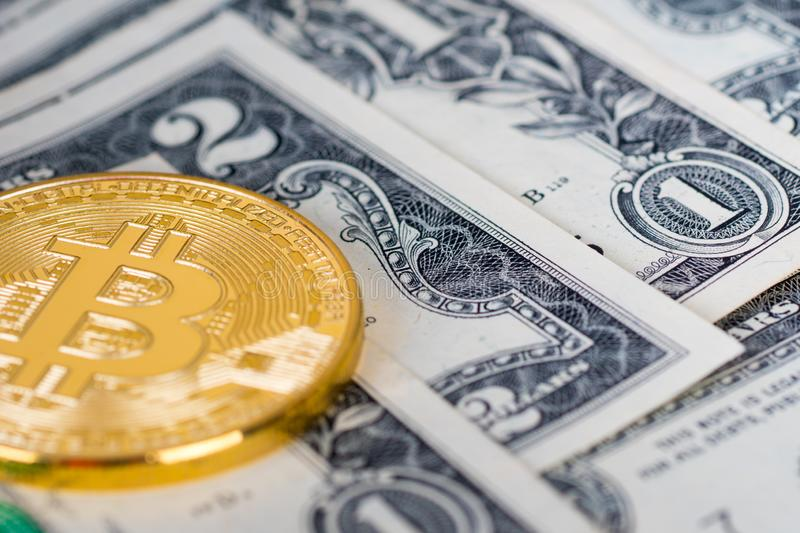 Bitcoin golden coin with dollars banknotes stock images