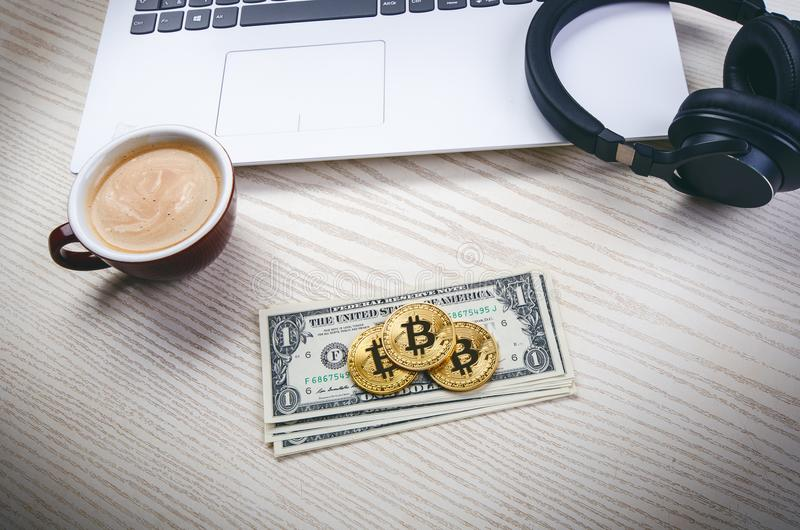 Bitcoin golden coins on a dollar banknotes. Office background. Cup of coffee, white laptop, mobile phone, and money. Money balance royalty free stock images