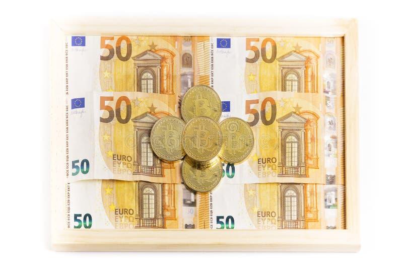 Bitcoin-Goldmünzen auf einem Kasten voll Eurorechnungen lizenzfreies stockfoto