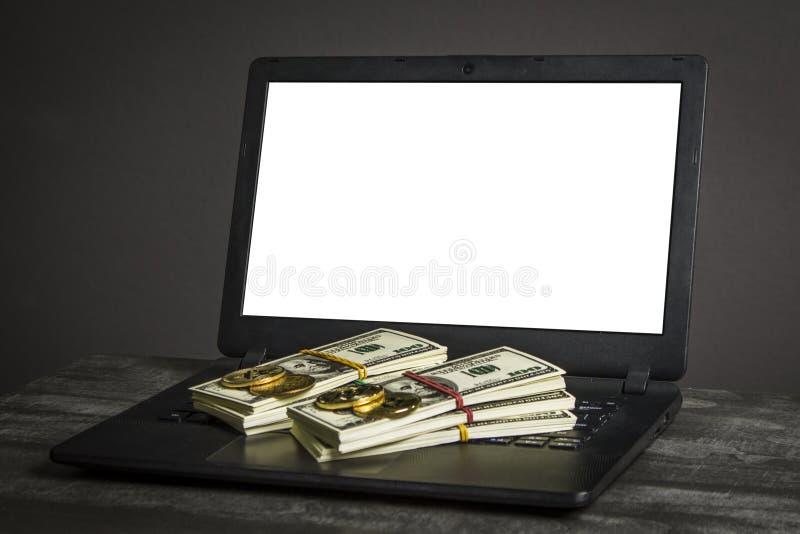 Bitcoin-Goldmünzen und Dollar auf Laptop lizenzfreie stockbilder
