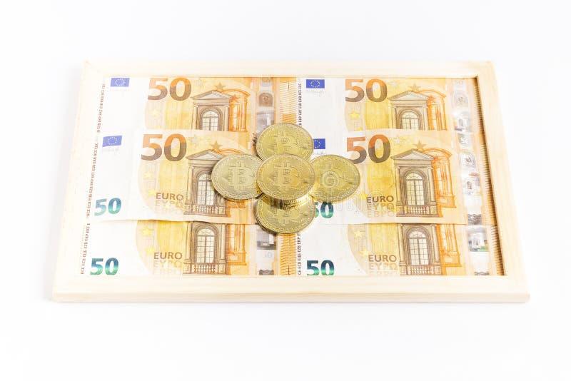 Bitcoin-Goldm?nzen auf einem Kasten voll Eurorechnungen lizenzfreie stockbilder