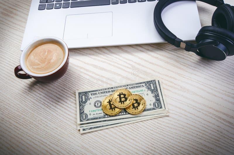 Bitcoin gouden muntstukken op een dollarbankbiljetten Bureauachtergrond Kop van koffie, witte laptop, mobiele telefoon, en geld G royalty-vrije stock afbeeldingen