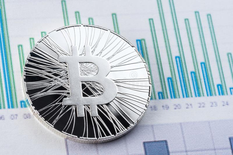 Bitcoin with graphics exchange rate on stock trade papers. Cryptocurrency, bitcoin invest chart royalty free stock images