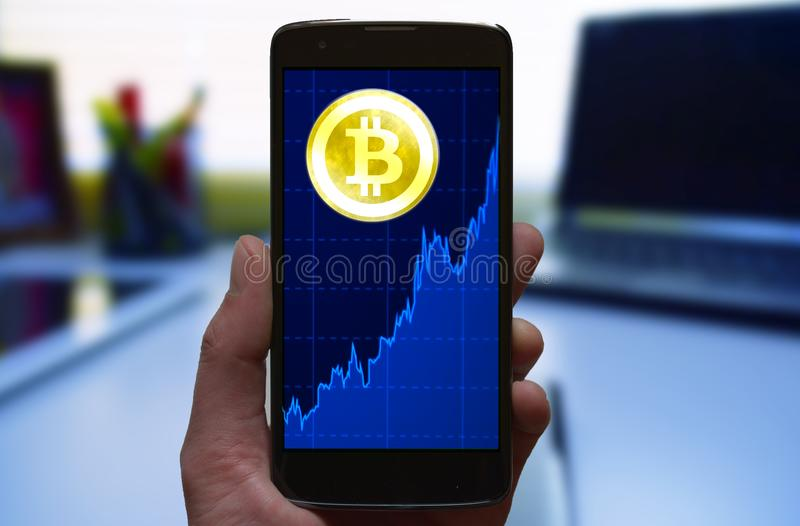 Bitcoin price growth graph. Cryptocurrency Bitcoin symbol and growth chart at the smartphone screen, smartphone in the hand. royalty free stock photo