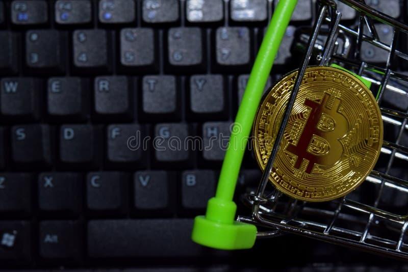 Bitcoin guld i shoppingvagn på tangentbordbärbar datorbakgrund Handel och affärsidé royaltyfri foto