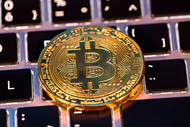 Bitcoin guld- mynt med bärbar datortangentbordet Faktiskt cryptocurrencybegrepp arkivbild