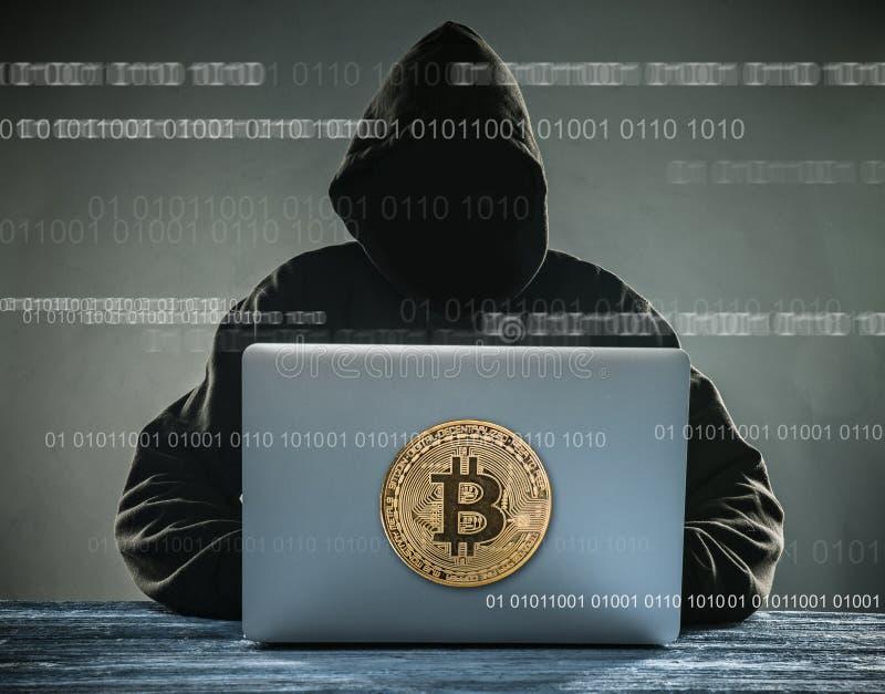 Bitcoin guld- mynt och anonym en hackersittign med bärbara datorn royaltyfri bild