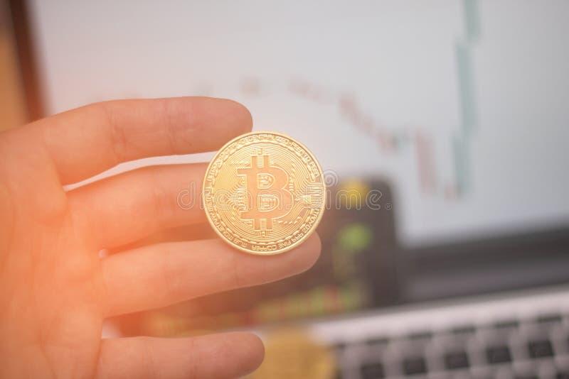 Bitcoin guld- mynt och defocused diagrambakgrund Faktiskt cryptocurrencybegrepp Manhåll i hand royaltyfri fotografi