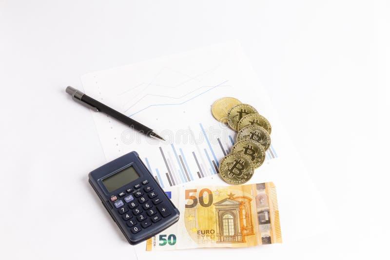 Bitcoin guld- mynt på graf bredvid en räknemaskin, en penna och en euroräkning arkivfoton
