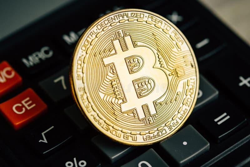Bitcoin guld- mynt på räknemaskintangentbordet Faktiskt cryptocurrencybegrepp arkivfoton
