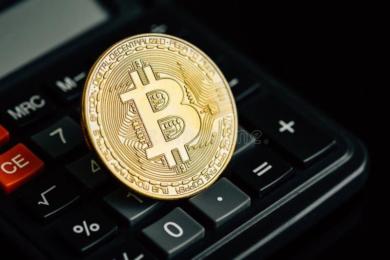 Bitcoin guld- mynt på räknemaskintangentbordet Faktiskt cryptocurrencybegrepp arkivfoto