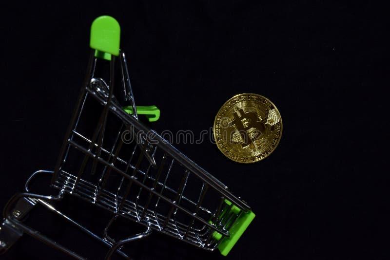 Bitcoin guld och shoppingvagn på svart bakgrund Bitcoin faller från ett begrepp för shoppa vagn arkivfoton