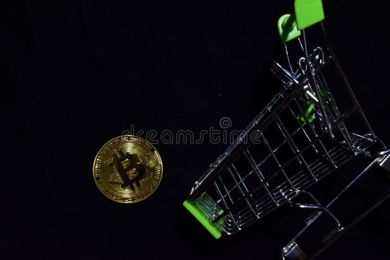 Bitcoin guld och shoppingvagn på svart bakgrund Bitcoin faller från ett begrepp för shoppa vagn royaltyfri bild