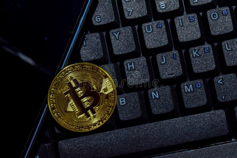 Bitcoin guld och smartphone på tangentbordbärbar datorbakgrund Handel och affärsidé arkivbild