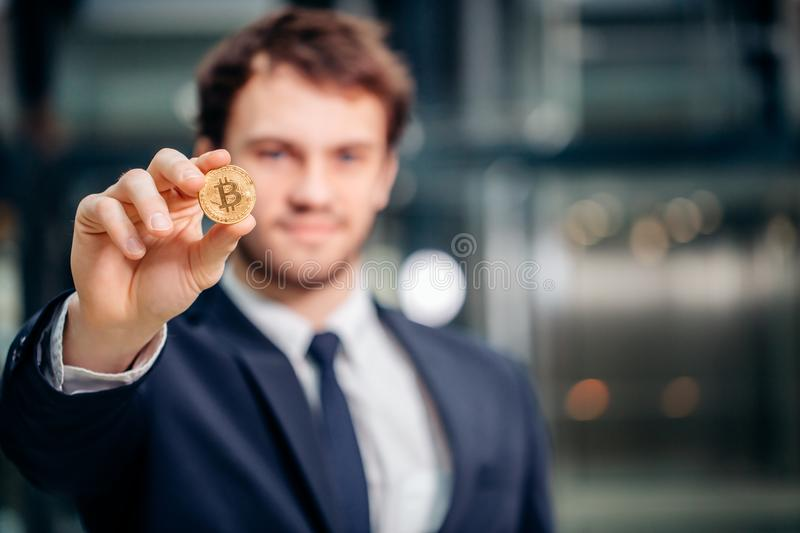 Bitcoin in hand with businessman blurred on background stock photography