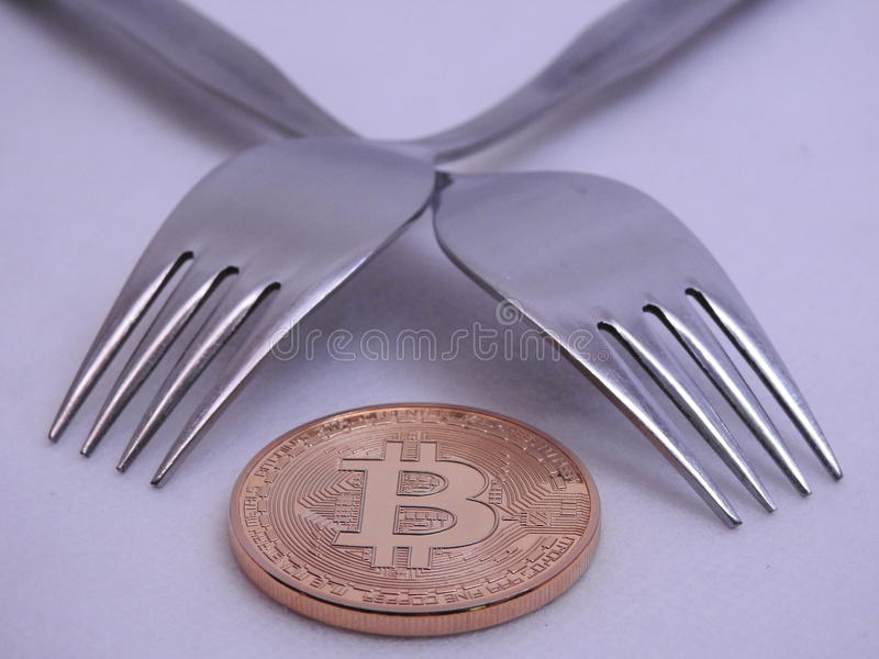 Bitcoin hard-soft fork. Bitcoin hard or soft fork to implement new rules in the block chain stock images