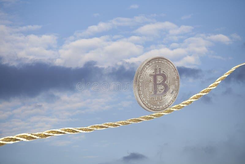 Bitcoin het in evenwicht brengen op gouden kabel stock afbeelding