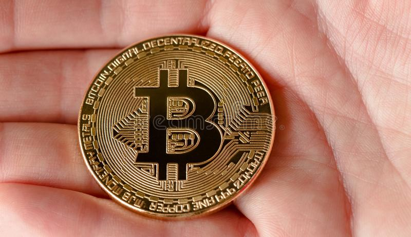 Bitcoin on the human hand close up. Physical bit coins. Digital currency. Cryptocurrency. Golden coins with bitcoin stock photos