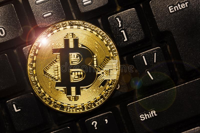 Bitcoin on keyboard. Physical bit coin. Digital currency. Cryptocurrency. Golden coin with bitcoin symbol. Bitcoin on keyboard. Physical bit coin. Digital stock photo