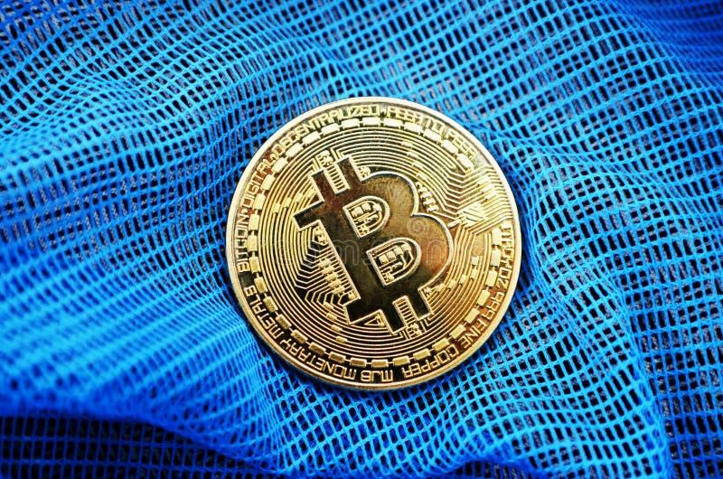 Bitcoin-Münze auf blauem Nettohintergrund lizenzfreies stockfoto