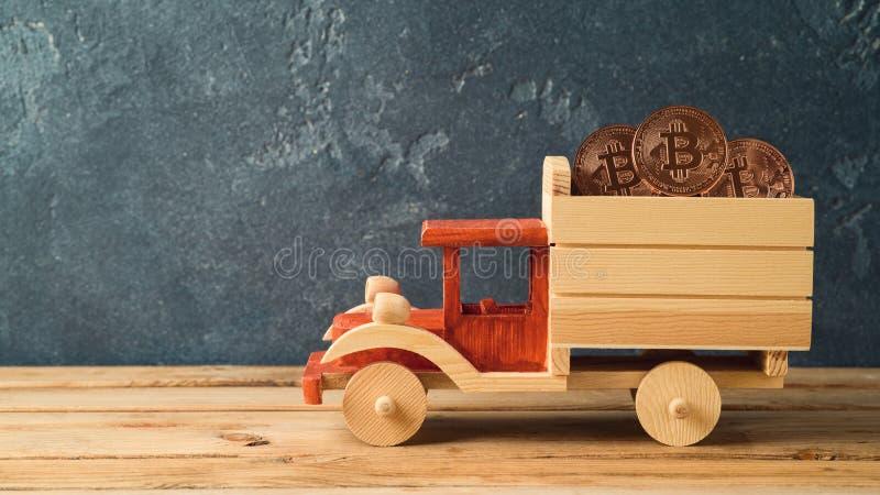 Bitcoin-Münze im Spielzeuglastwagen auf Holztisch lizenzfreies stockbild