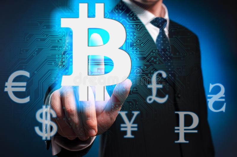 Bitcoin. A man in a suit and tie clicks the index finger on the stock photo