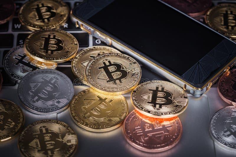 Bitcoin med mobilen på en bärbar datortangentbordbakgrund royaltyfri foto