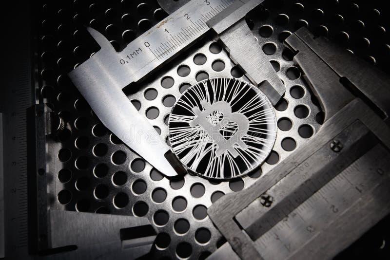 Bitcoin midió con el calibrador en fondo del metal Concepto de cryptocurrency virtual internacional fotografía de archivo