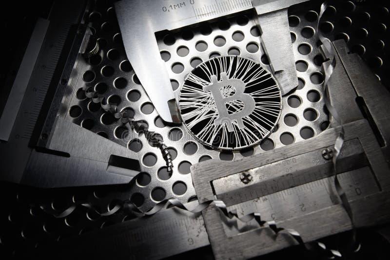 Bitcoin midió con el calibrador en fondo del metal Concepto de cryptocurrency virtual internacional fotos de archivo