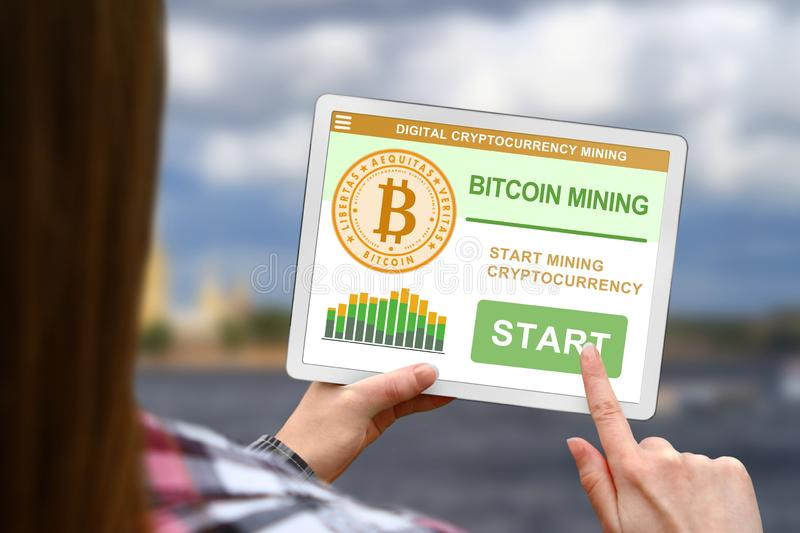 Bitcoin mining concept, girl holds the digital tablet on blurred clouds background royalty free stock image