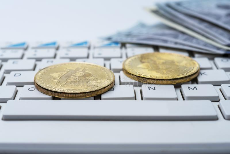 Bitcoin mynt med tangentbordet och US dollar Bitcoin guld- mynt på dollarsedelkontor med en vit bakgrund arkivfoton