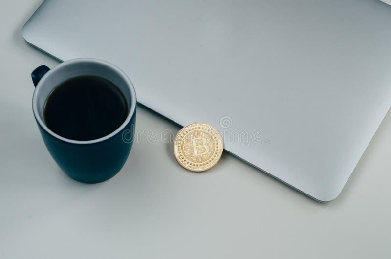 Bitcoin mynt nära den gråa bärbar dator- och blåttkaffekoppen Cryptocurrency begrepp Isolerat på vit royaltyfria bilder