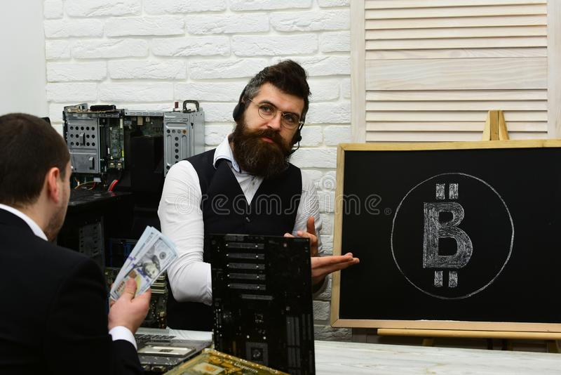 Bitcoin nahm hier an Geschäftsmänner am Schreibtisch Bärtiger Mannpunkt an bitcoin Symbol Kundengriffbargeld stockbilder