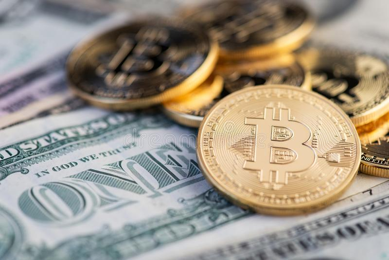 Golden Bitcoin on US dolllar close up. Bitcoin virtual money and banknotes of one dollar. royalty free stock photo
