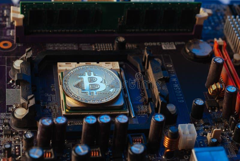 Bitcoin no cartão-matriz, moeda virtual no fundo da placa eletrônica, imagens de stock