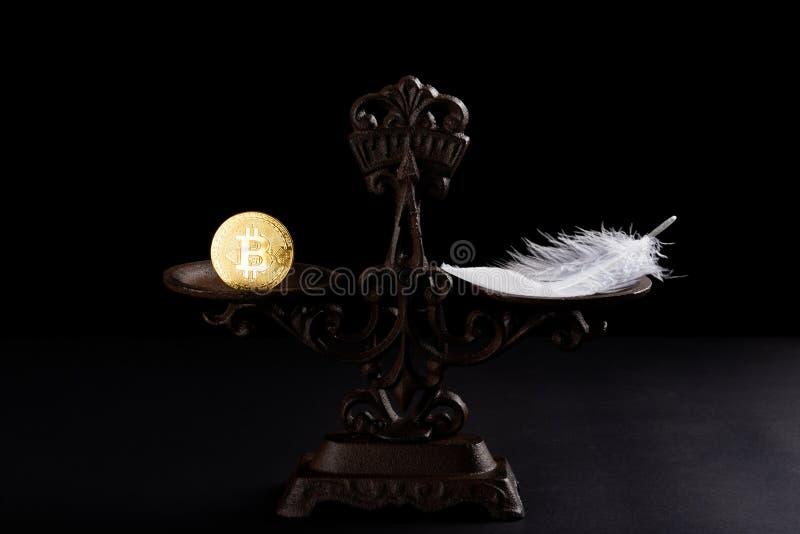 Bitcoin och fjäder på en allsidig skala arkivbild