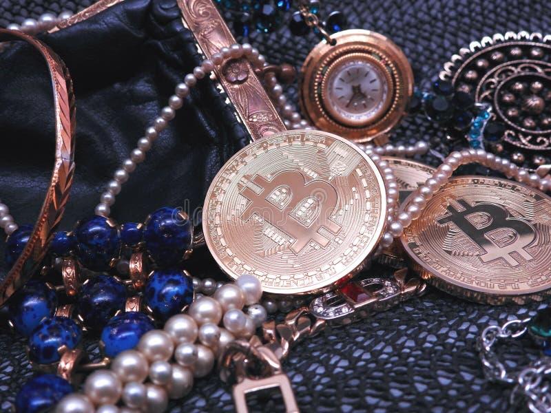 Bitcoin och juvlar som finnas i en handväska royaltyfri foto