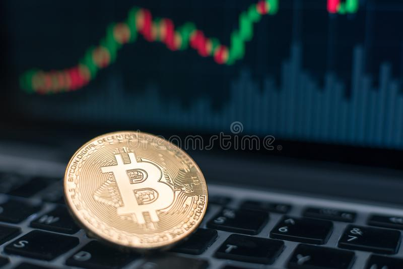Bitcoin Physical Coin Symbol On Laptop With Uptrend Price Graph