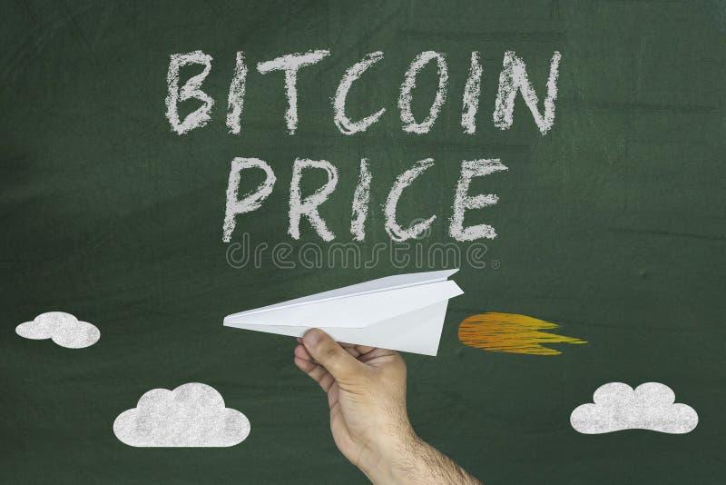 Bitcoin-Preissteigerungskonzept mit der Hand, die Papierfläche auf Tafel hält stockfoto