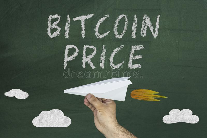 Bitcoin Price Boosts concept with hand holding paper plane on chalkboard stock photo