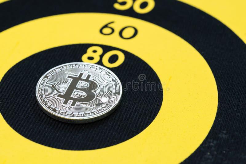 Bitcoin price target, physical bitcoin coin on center of yellow circle dartboard.  stock photography