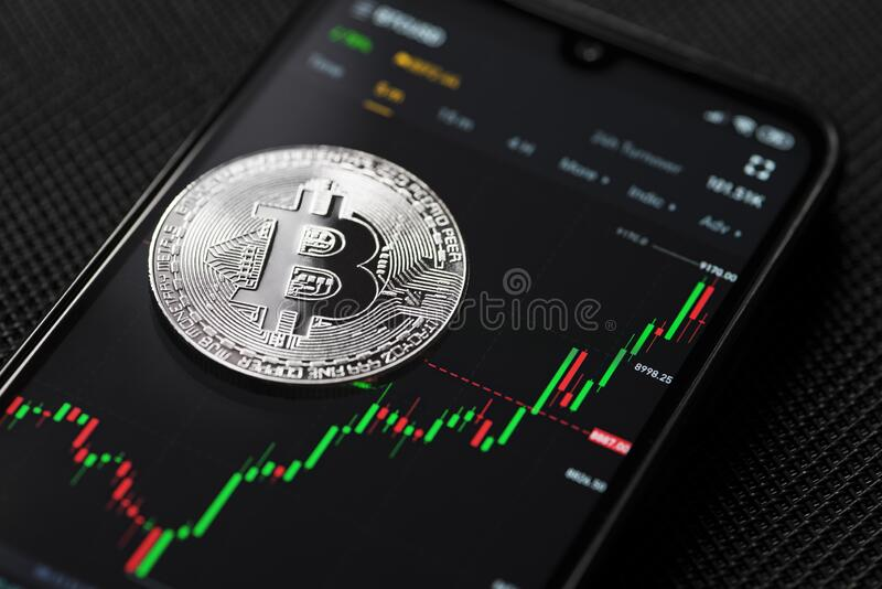 Silver bitcoin coin with chart background royalty free stock photography
